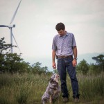 man with a dog and wind turbine in the background