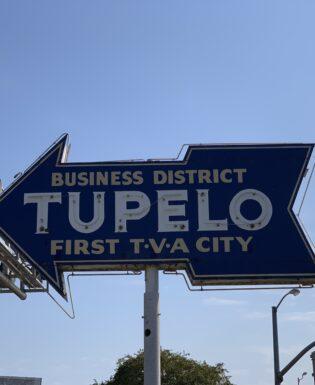 """neon arrow sign that says """"Tupelo"""""""